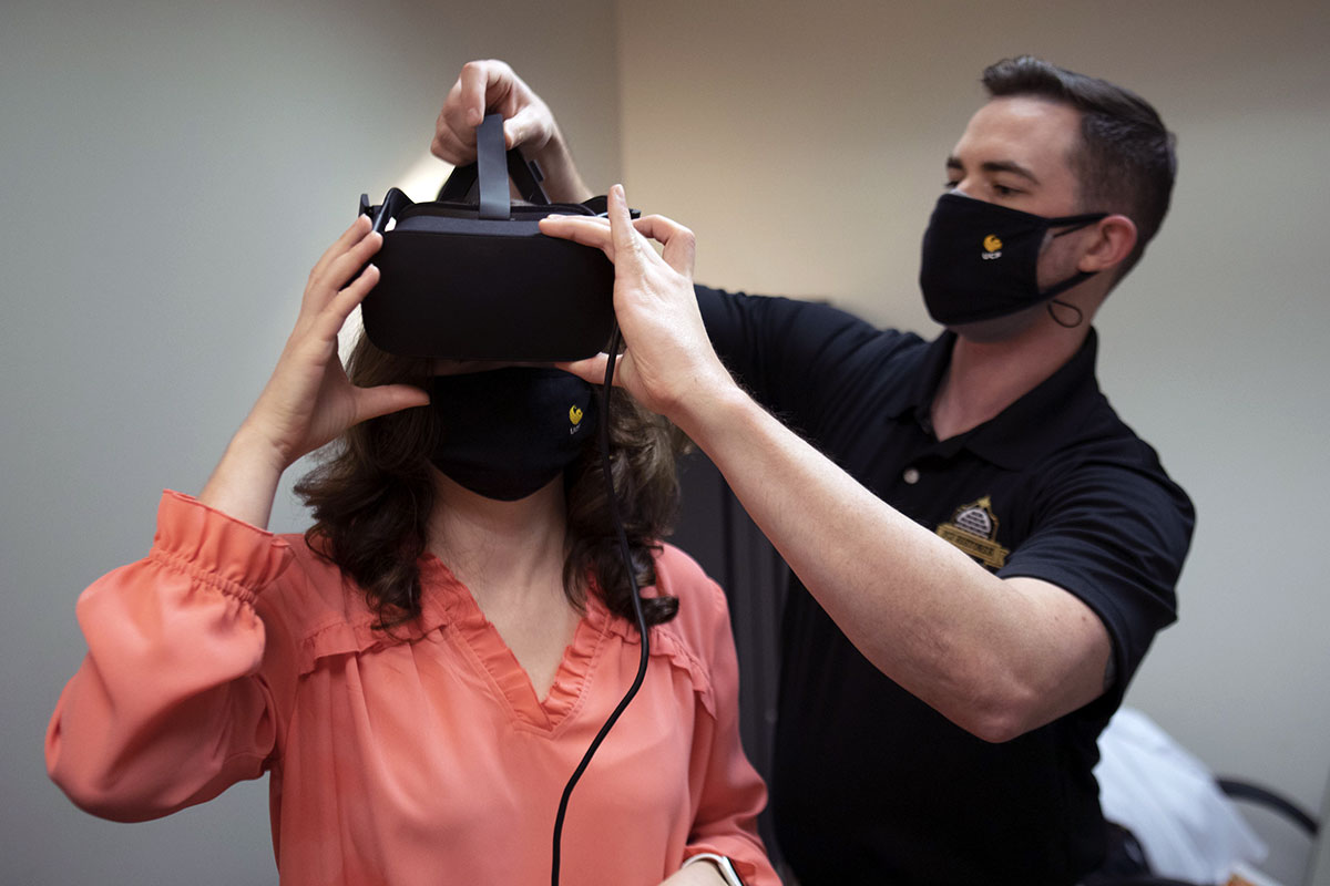man helps fit a woman with a VR headset
