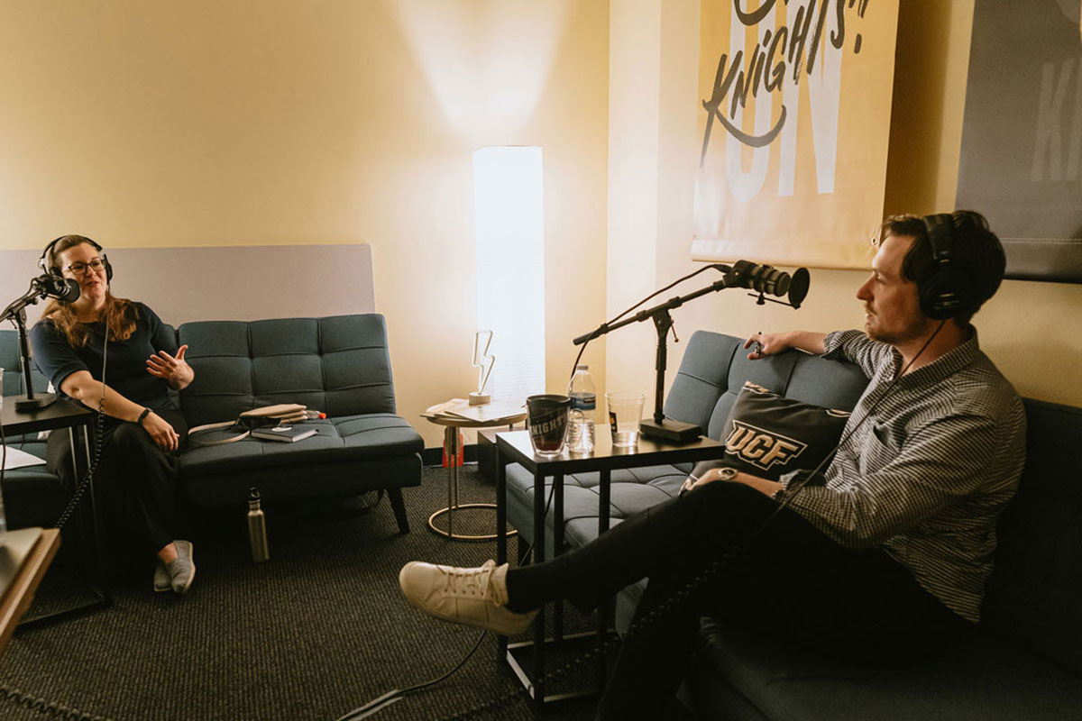 Claire Connolly Knox and Alex Cumming sit on sofas recording podcast