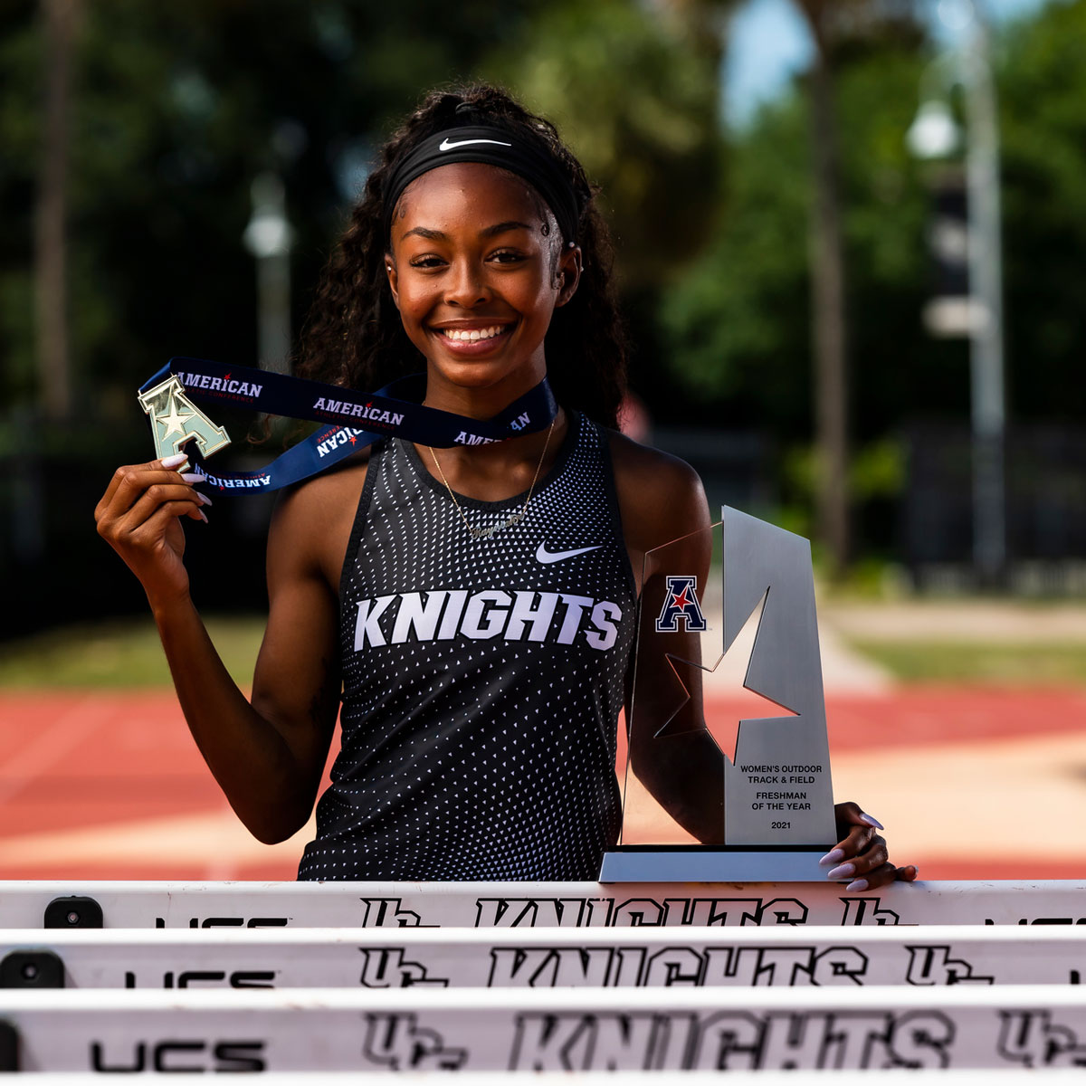 Rayniah Jones stands near hurdles, holding AAC medal and trophy