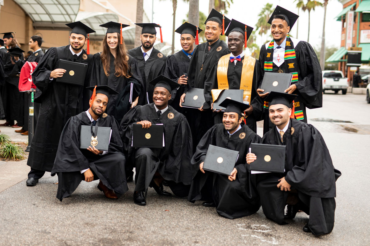 Group of 11 graduates pose with their diplomas in hand outside of Addition Financial Arena