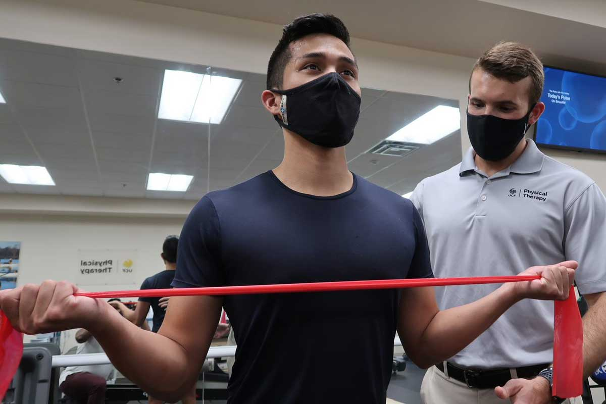 Man stretches red resistance band as a physical therapist observes form