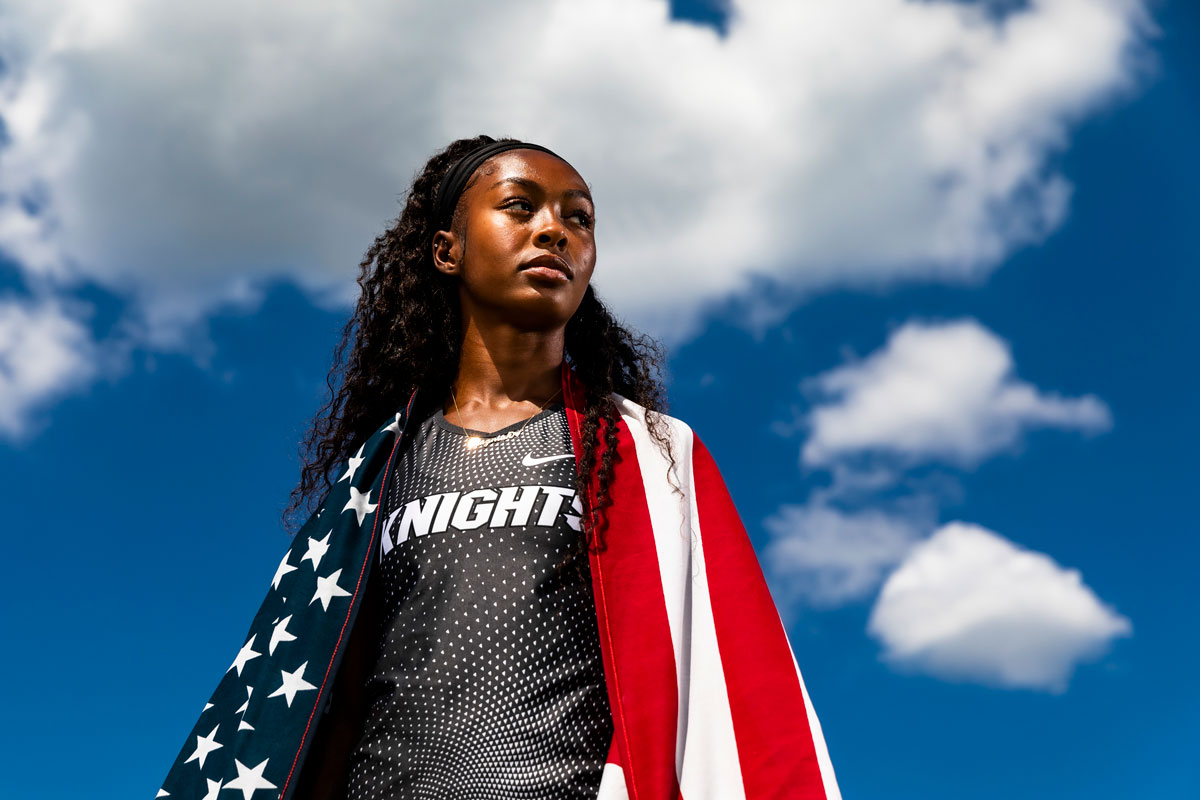 Rayniah Jones in gray Knights uniform with USA flag draped over her shoulders