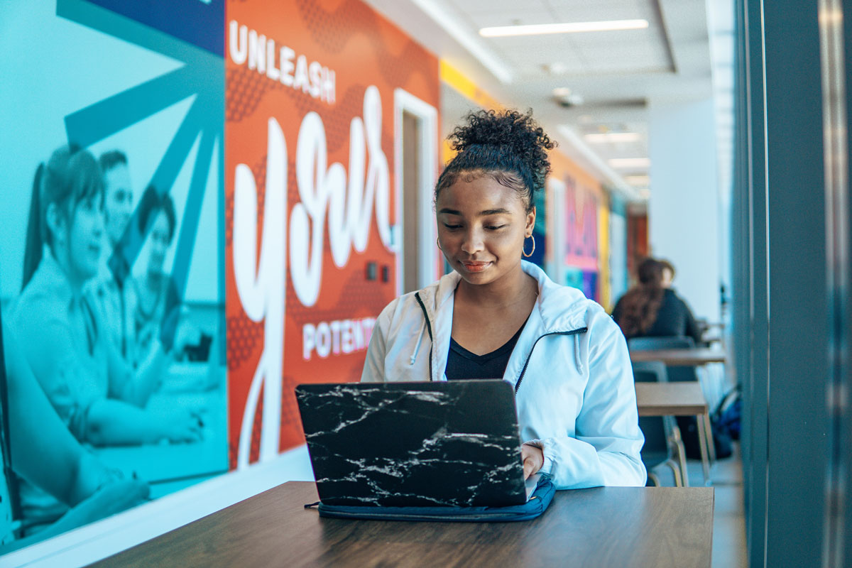 young woman sits with laptop opened in front of her in a hallway