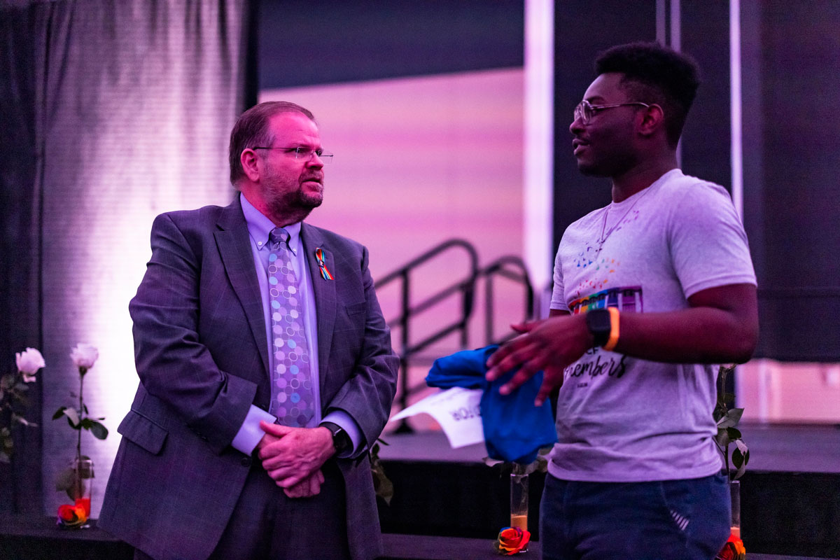 President Catwright speaks with a student in front of the stage