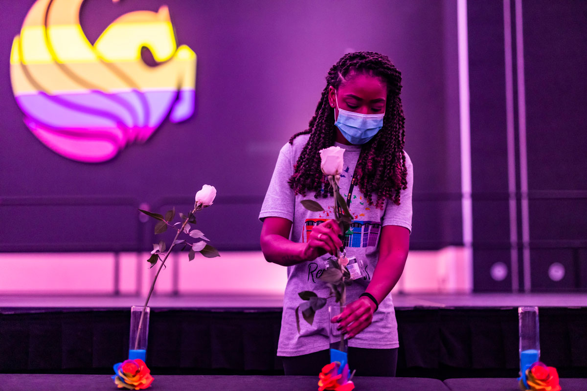 Black woman wearing face mask places a rose in a vase with a rainbow Pegasus logo in the background