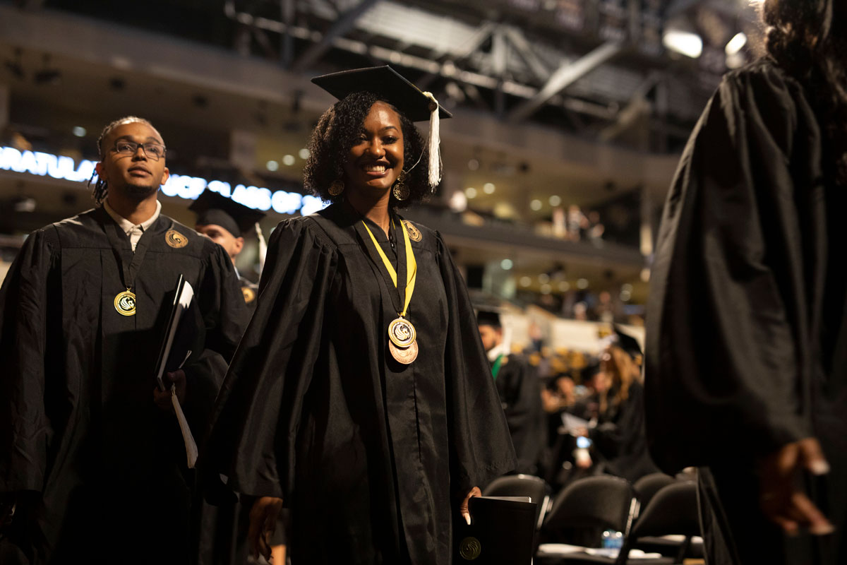 Black woman student in cap and gown smiles at the camera