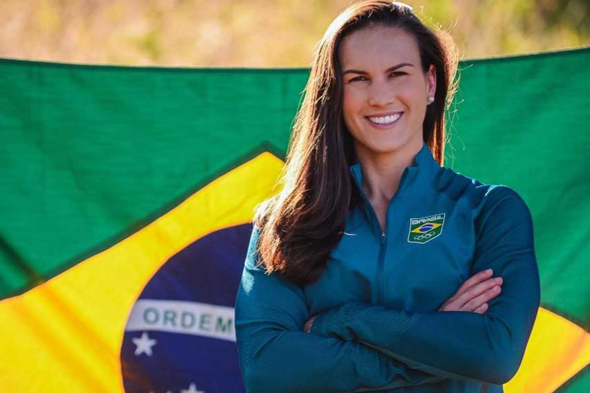 Aline Reis stands with arms crossed in front of Brazilian flag