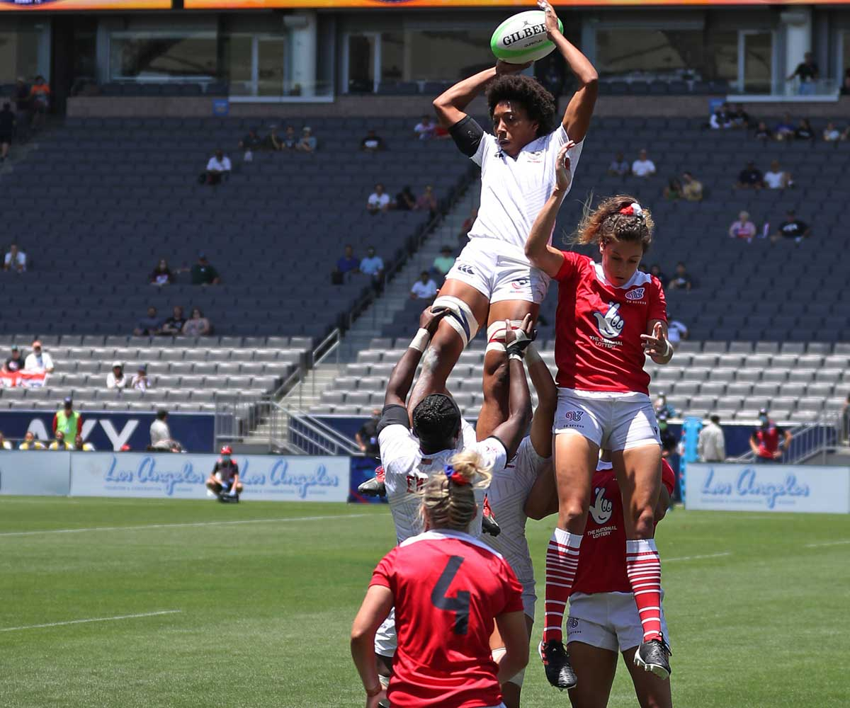 Kristen Thomas midair in a scrum of Rugby players