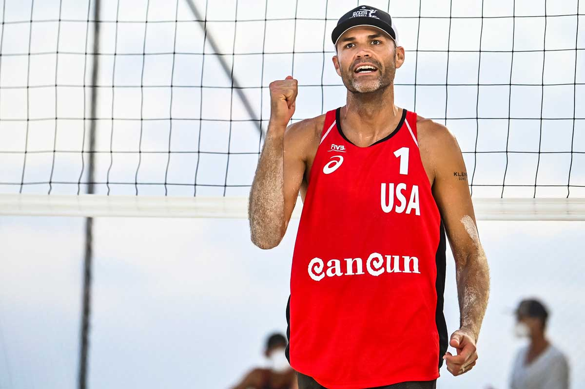 Phil Dalhausser in red jersey clinches fist in front of net