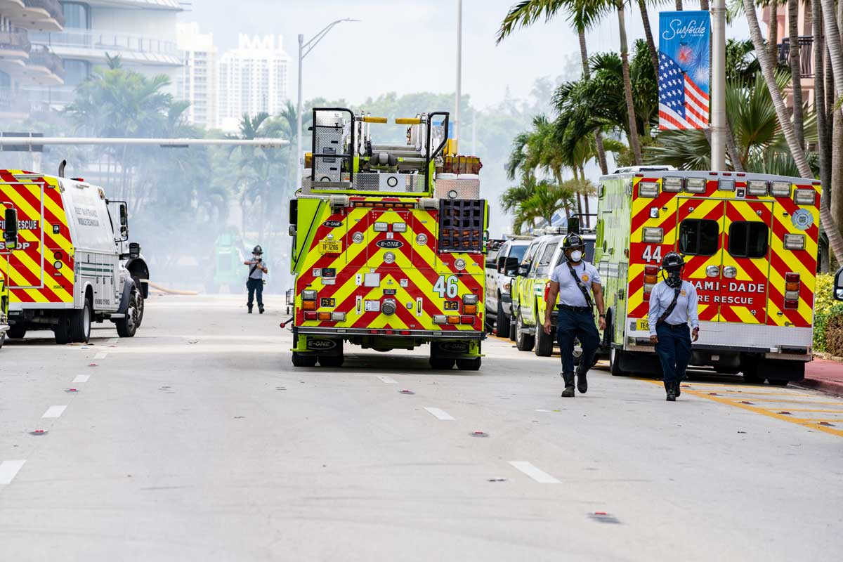 Miami Dade emergency response vehicles parked on dusty street with two first responders walking nearby