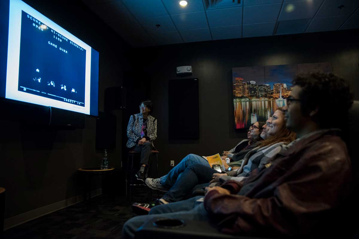 """Students sit in a row of seats while observing a screen with a video game message """"game over"""""""