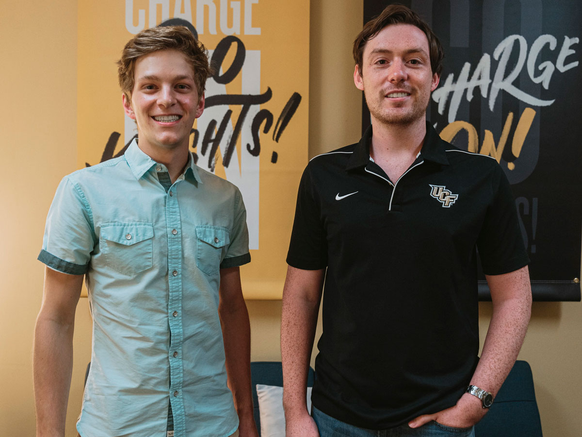 Daniel West and Alex Cumming stand in front of Go Knights Charge On signs
