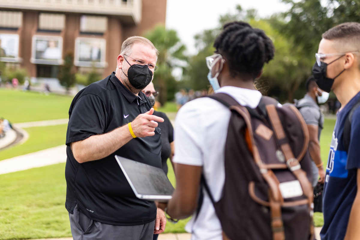Alex Cartwright wearing a black face mask talks to two male students near Reflecting Pond
