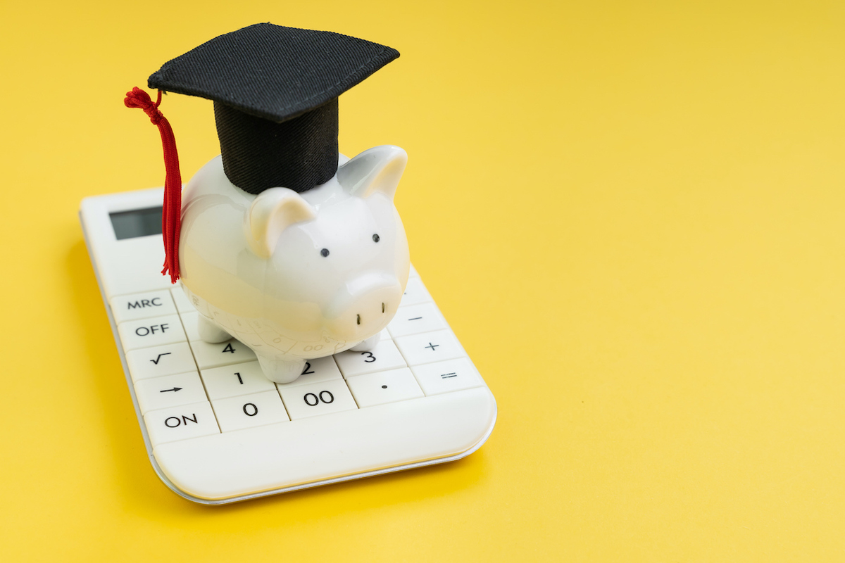 Student loan payment calculation, scholarship or saving for school and education concept, white piggy bank wearing graduation hat on calculator on yellow background with copy space. (Student loan payment calculation, scholarship or saving for school a