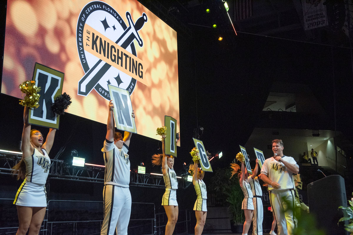 Members of cheer team hold up signs spelling KNIGHTS on stage with a Knighting banner illuminated behind them