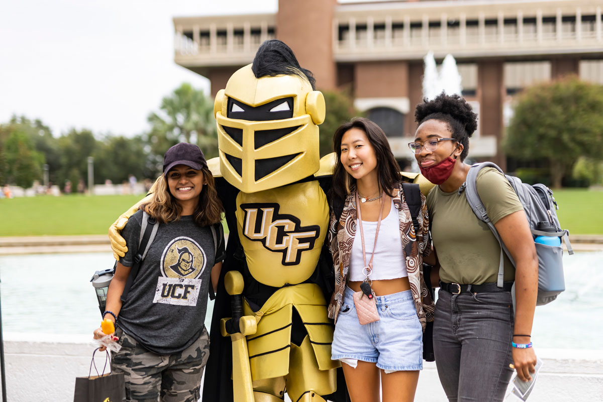 Knightro poses for a photo with three women students