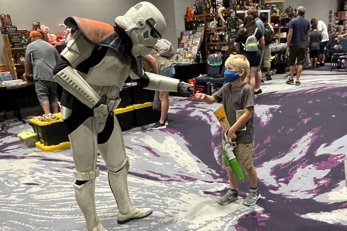 Sandtrooper fist bumps with a young blonde child