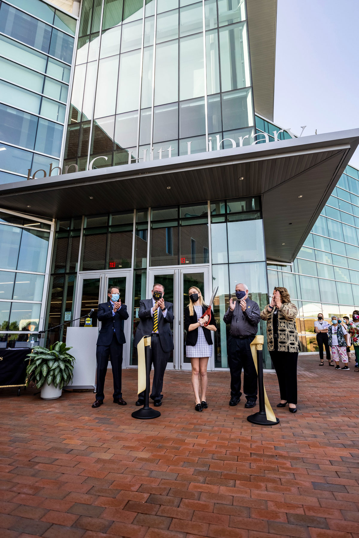Five university leaders stand at the entrance of John C. Hitt Library after cutting a ribbon for grand opening