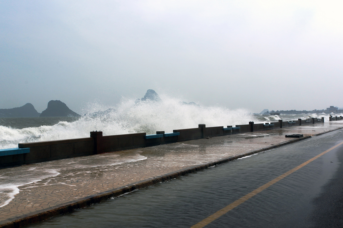 waves breaking against a wall with a street running by