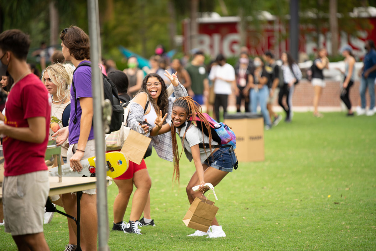 Students pose with funny faces on Memory Mall while people mill about around them