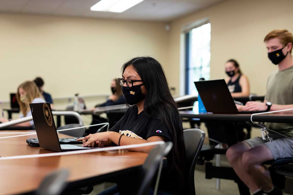 A group of students wearing masks sit at desks in lecture hall