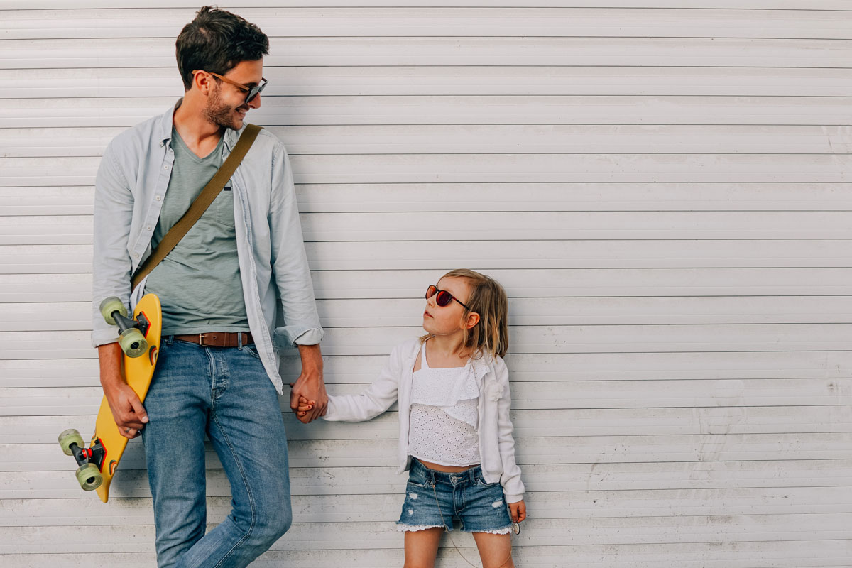 Dad holds skateboard while holding daughter's hand
