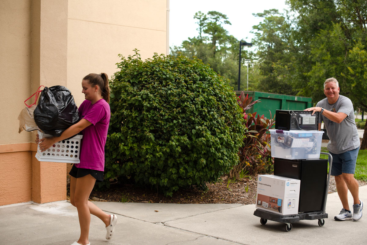 A woman in a pink shirt carries a laundry basket packed with belongings while her father wheels a cart of belongings behind her