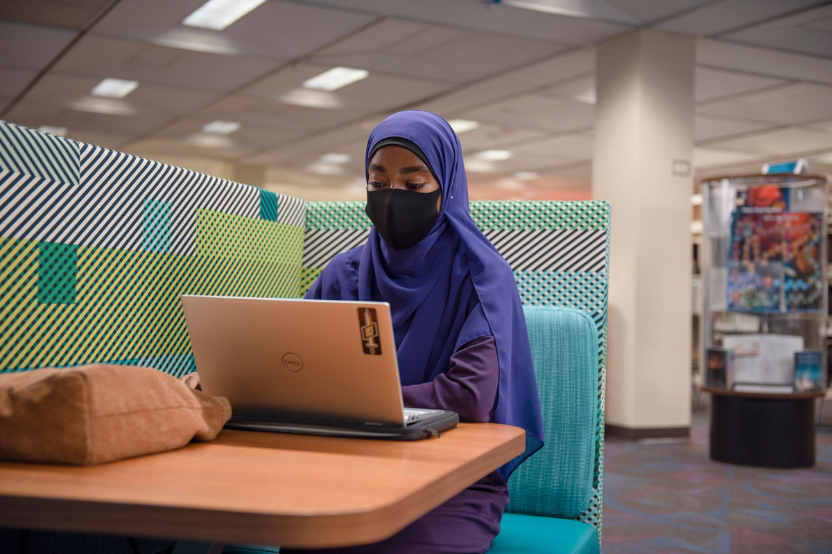 Student wearing purple hijab sits at a table with a laptop in John C. Hitt Library
