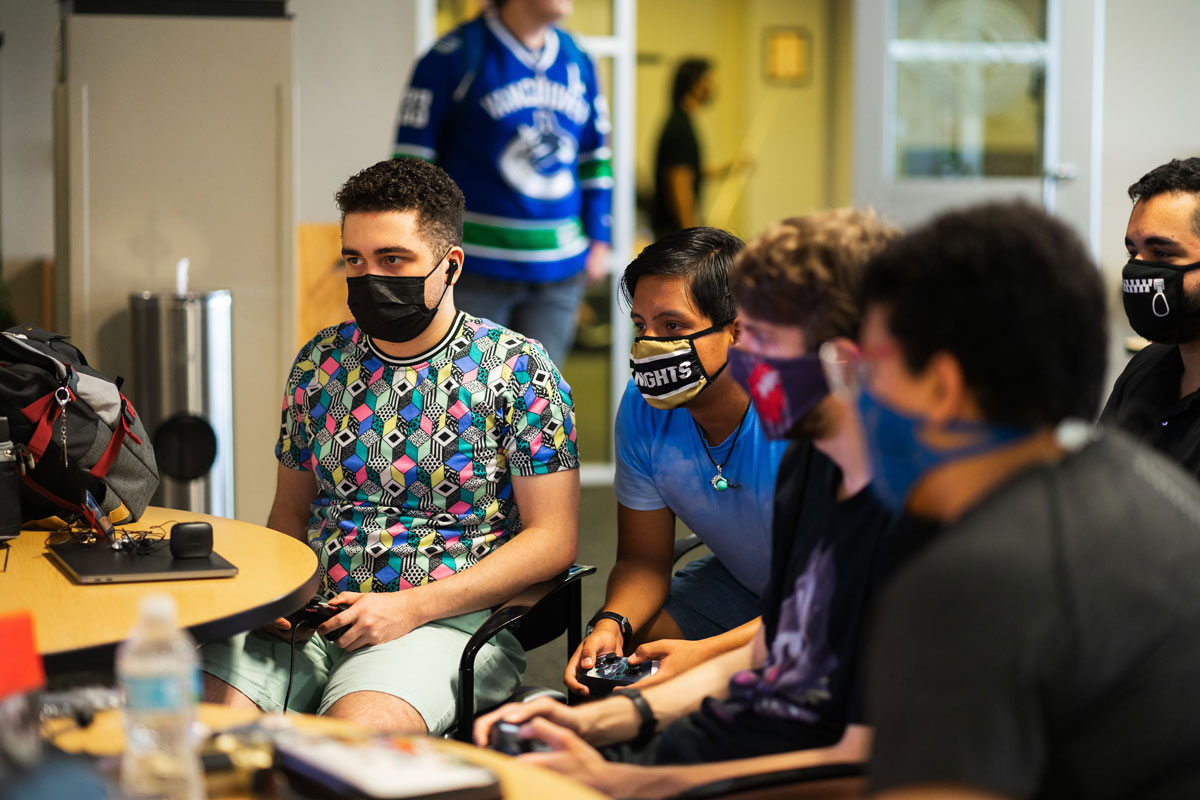 Four students play a video game on third floor of Student Union