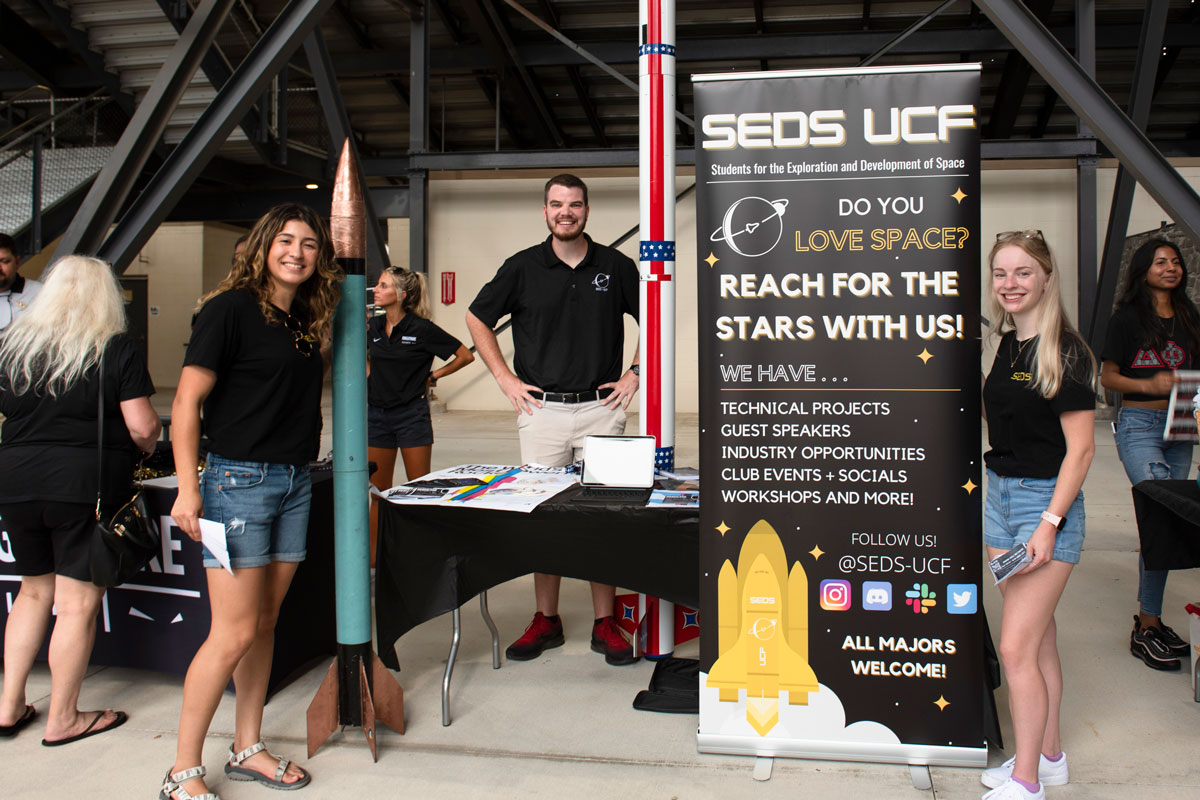 Three students pose with SEOS UCF banner and table