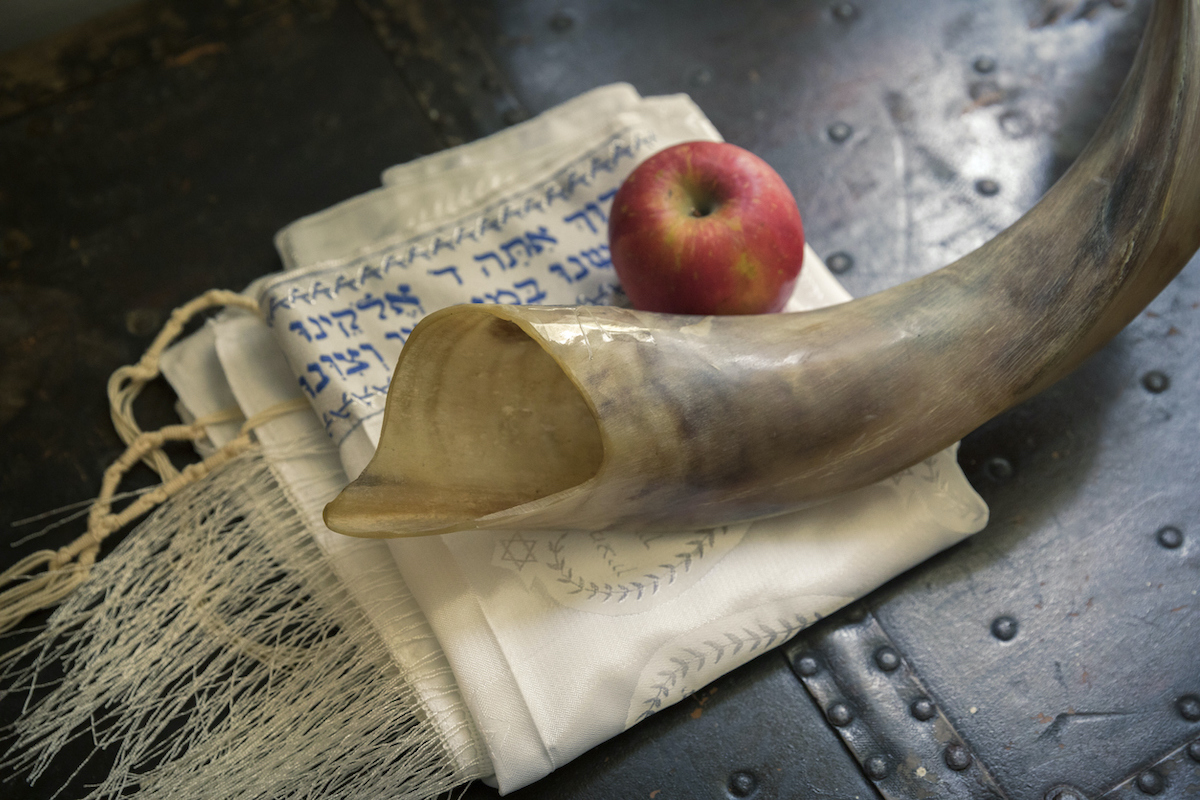 Close up of shofar ,Hebrew prayer book and apple on a table