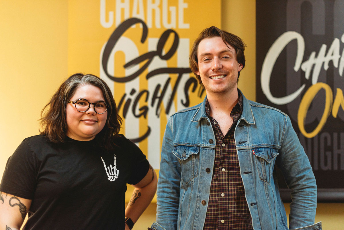 Reina Castellanos and Alex Cumming in front of Go Knights Charge On black and gold wall banners