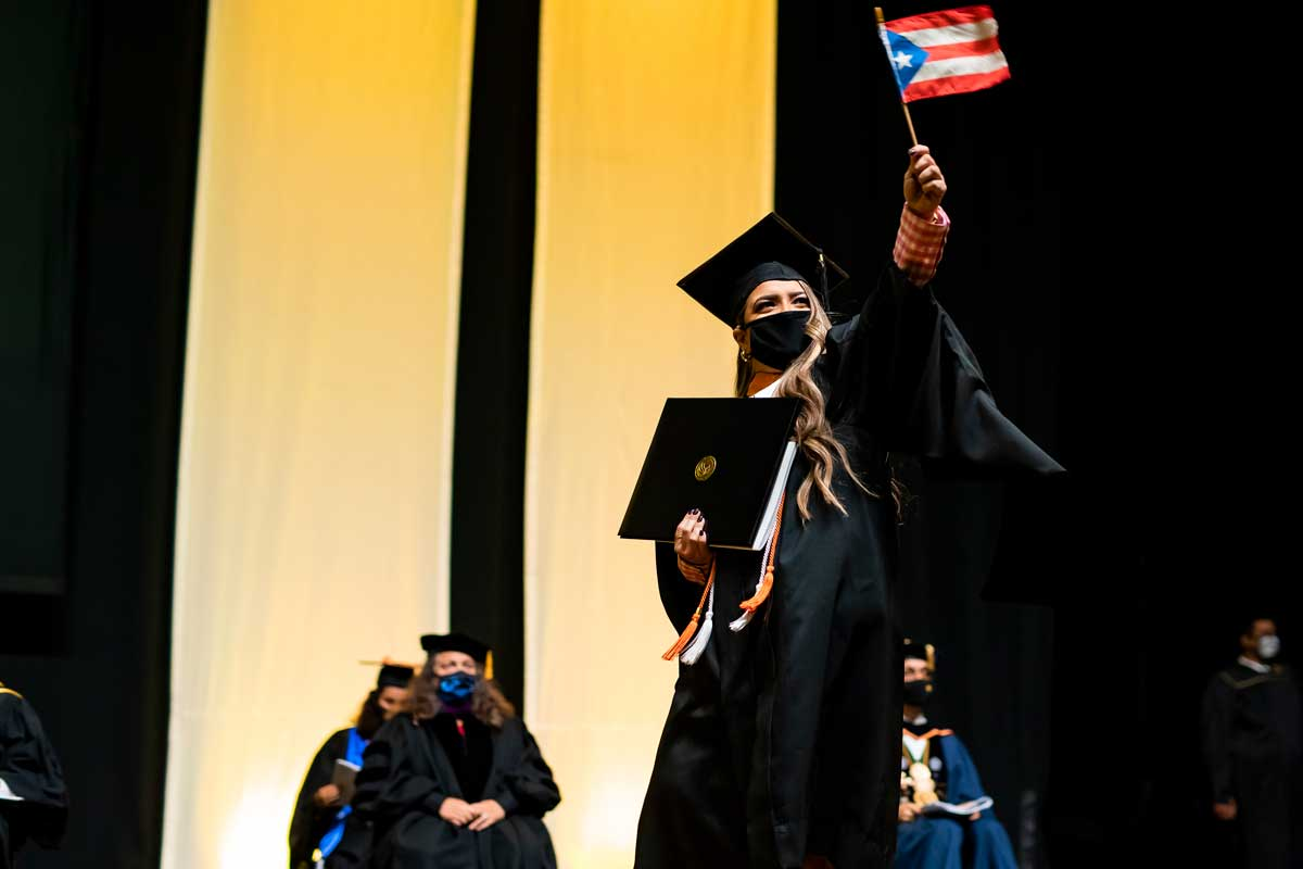 UCF grad waves a Cuban flag as she crosses the stage at commencement