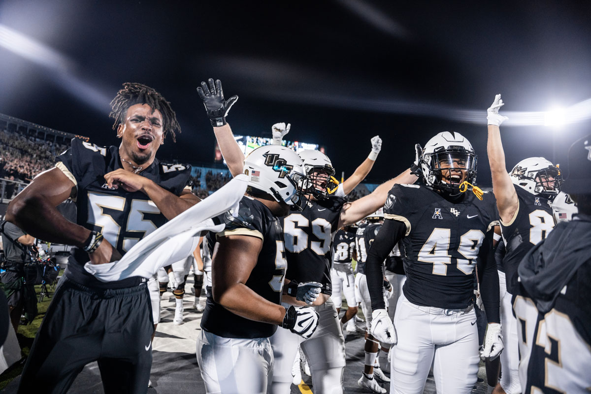 A group of football players cheer on the sidelines
