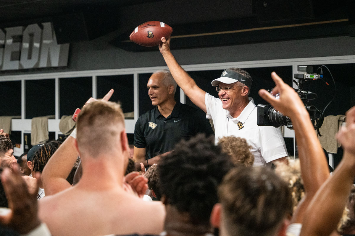 Gus Malzahn holds up a football in celebration with Terry Mohajir standing next to him in locker room