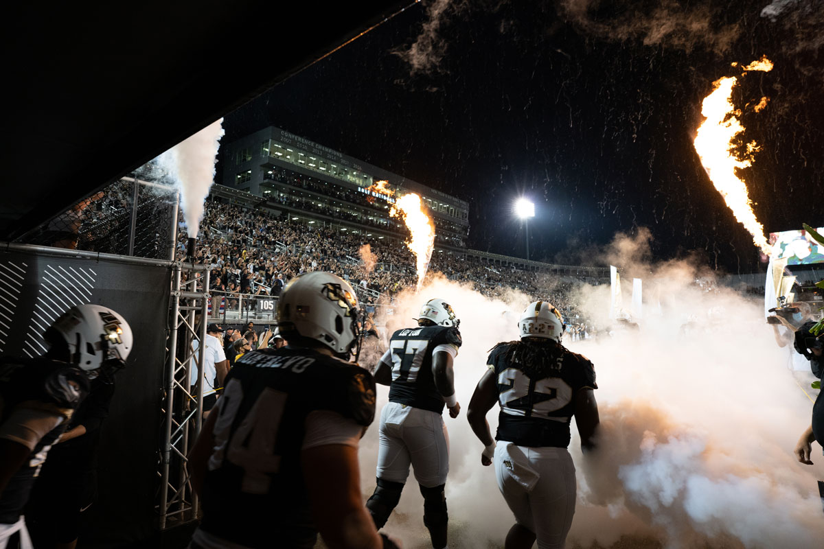 UCF football players leave the tunnel to run out to the field with fireworks shooting off