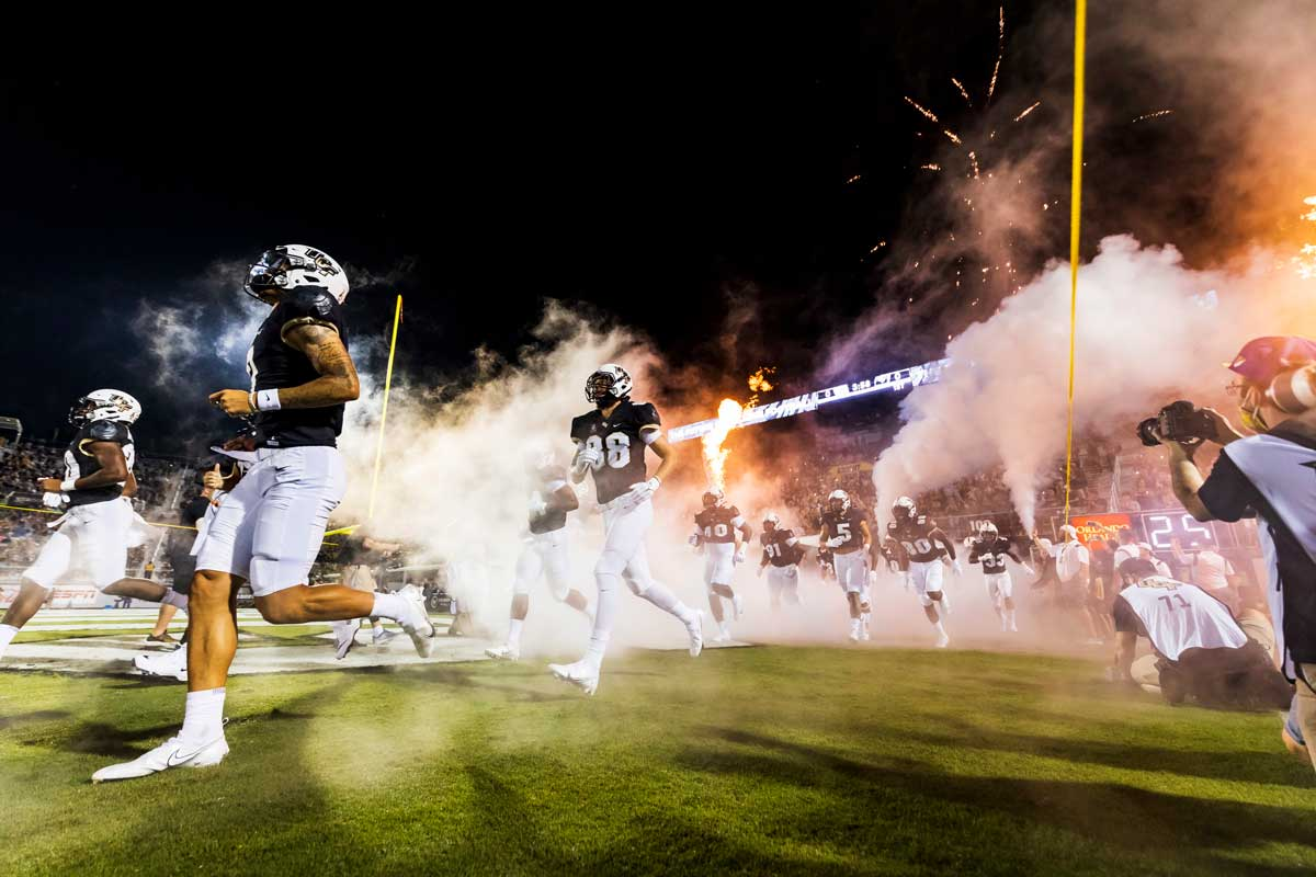 UCF football players run onto the field from locker room tunnel at night with fireworks shooting off