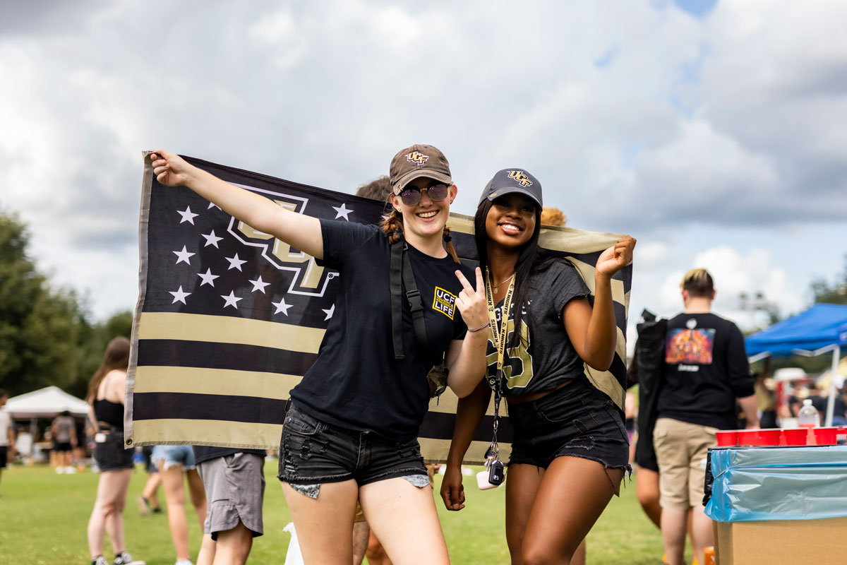 Two women pose with a UCF flag on Memory Mall