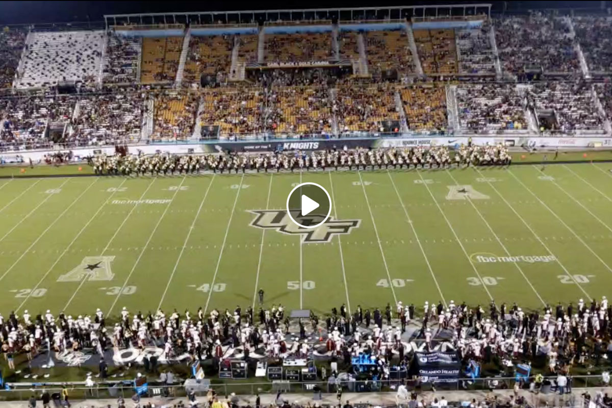 Screen shot of football field with bands on the sidelines and a play button in the middle