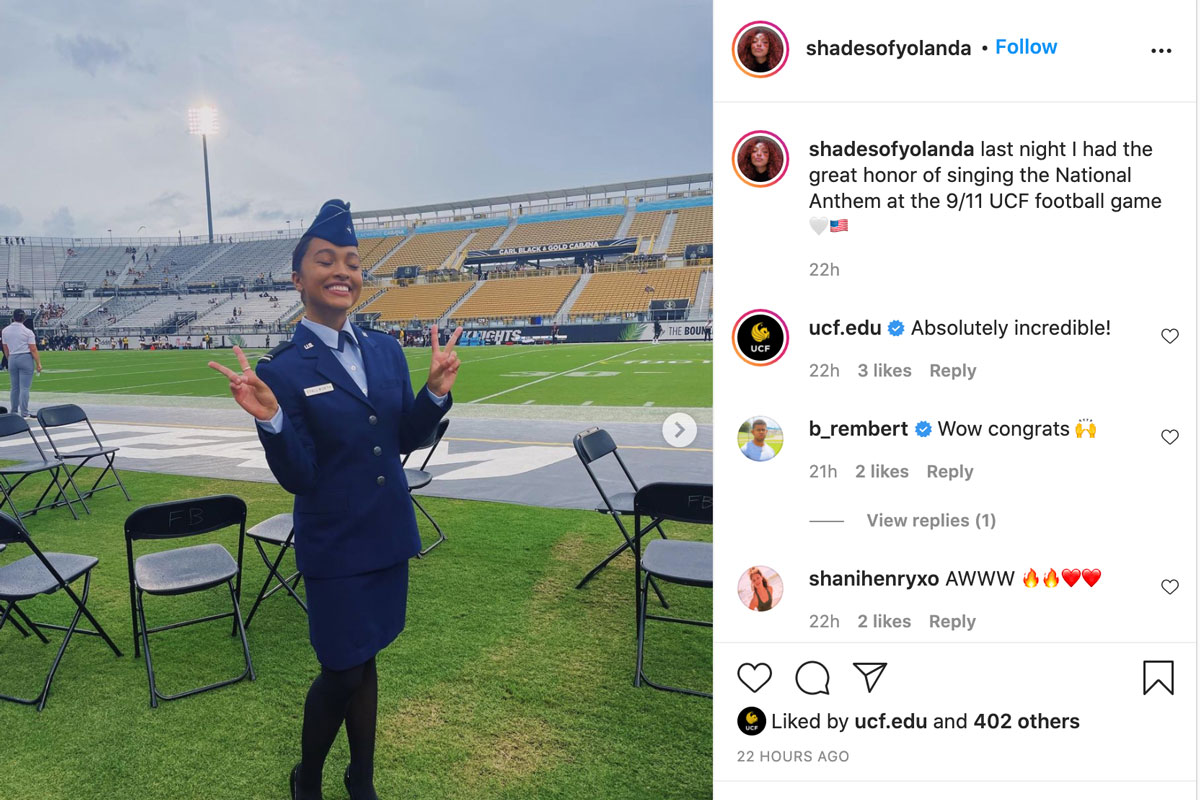 Young woman in air force blue uniform poses on sideline of football field