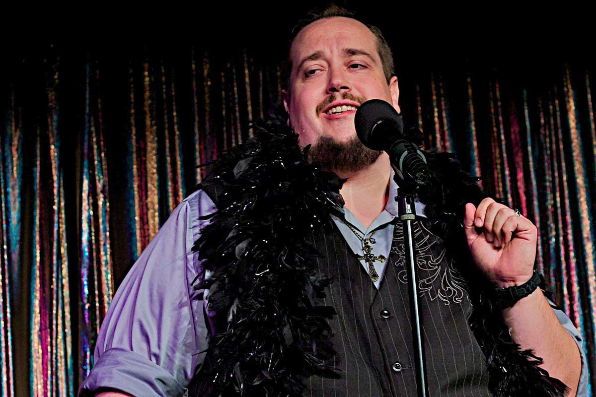 Daniel Jones with a feather boa around his neck, at a microphone