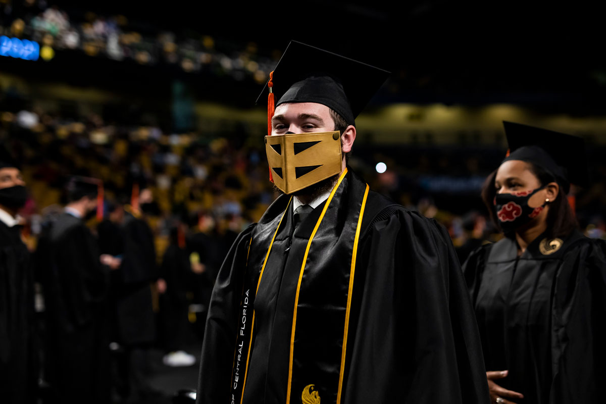 Male UCF grad in cap and gown wears a Knightro mask