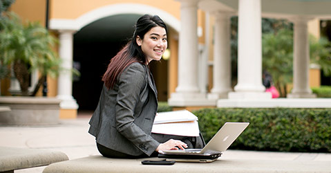 A female student sitting on a bench with laptop on the University of Central Florida campus