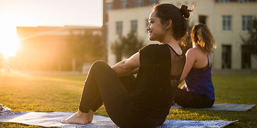 female ucf students practicing yoga on memory mall