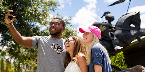 group of ucf students taking a selfie in front of a statue of a knight on horse