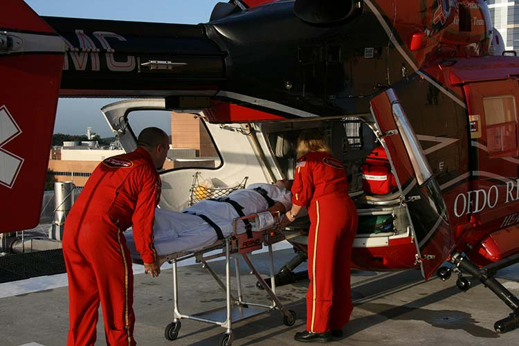 EMTs load a patient on a helicopter