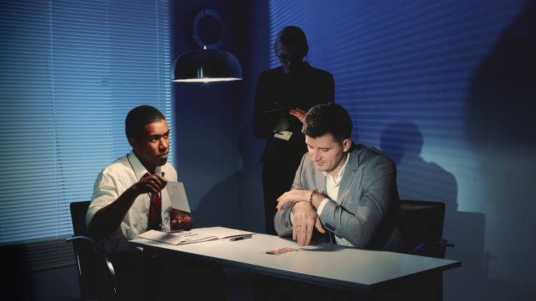 A police detective questions a suspect in an interrogation room.
