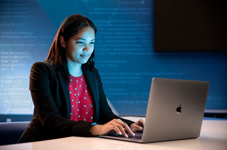 Database engineer working on her laptop in a data center.