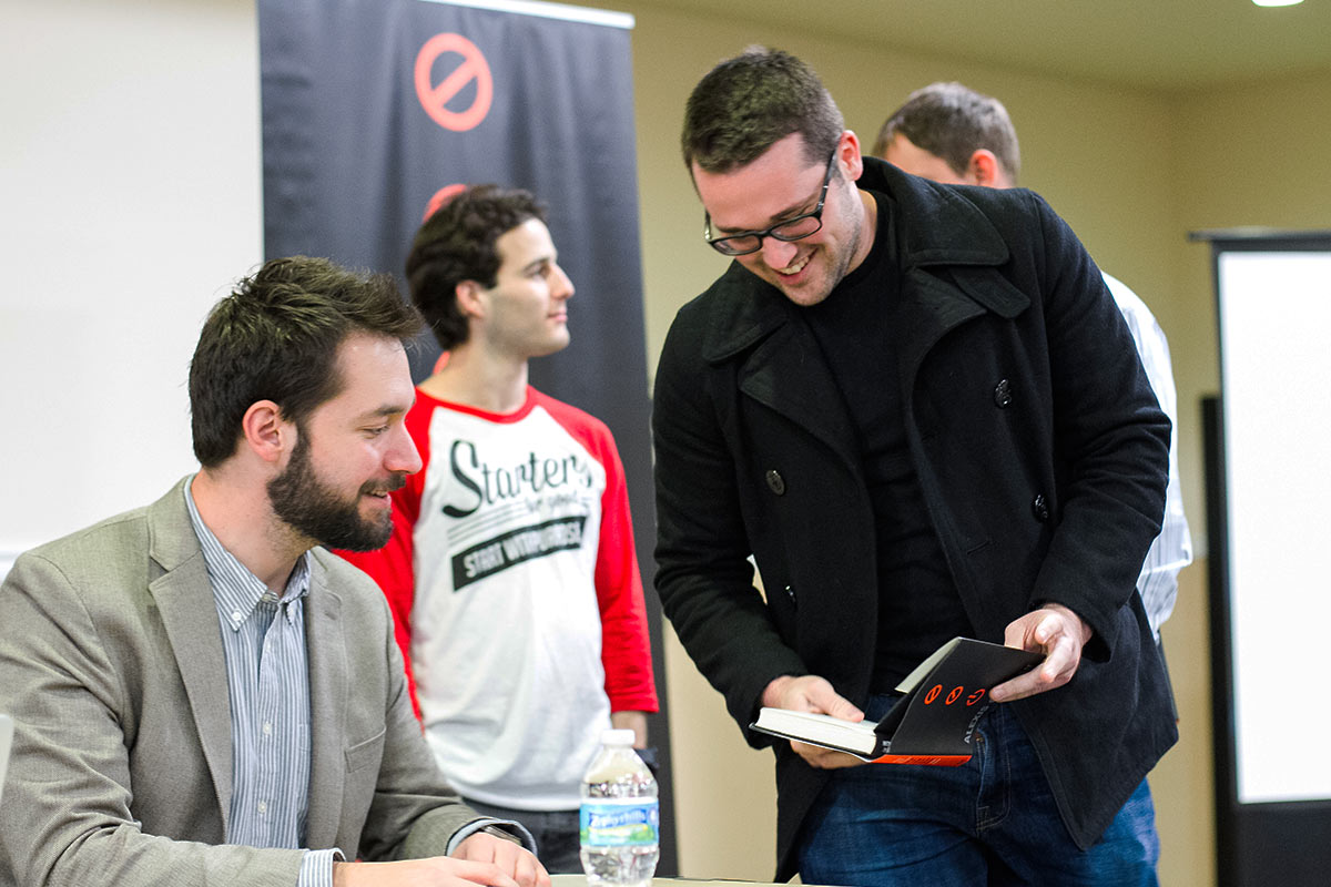 Alexis Ohanian, co-founder of Reddit, autographs a book