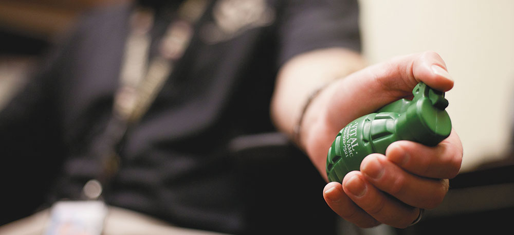 U.S. Department of Veterans Affairs psychologist Bryan Batien hands out stress relief squeeze toys shaped like hand grenades at the Veterans Academic Resource Center.